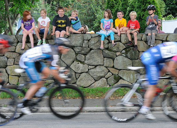 PAUL BILODEAUS/Staff photo.  A group of children watch on a wall on the corner of Dane and Hale Streets  during the Gran Prix of Beverly held last night downtown Beverly. 7/30/14