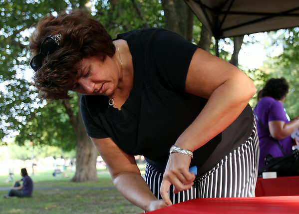 Elizabeth O'Hara, of Eastern Bank, tapes a plastic table cloth to a table while setting up for the Ice Scream Bowl on Salem Common on Tuesday afternoon. DAVID LE/Staff photo. 8/5/14.