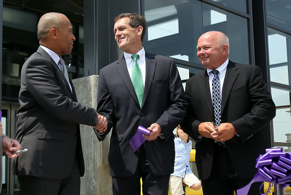 Governor Deval Patrick, left, shakes hands with Beverly Mayor Mike Cahill, as George Doherty, Project Manager for the MBTA, looks on, after a ribbon cutting ceremony to officially open the new Beverly Depot Parking Garage on Friday afternoon. DAVID LE/Staff photo. 8/1/14.
