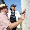 Salem Mayor Kim Driscoll and City Councillor Bill Legault examine the side of the lighthouse on Bakers Island following a short ceremony in which the deed to part of the island, which includes the lighthouse, was transferred from the US Coast Guard to the Essex National Heritage Commission on Wednesday morning. DAVID LE/Staff photo. 8/27/14.