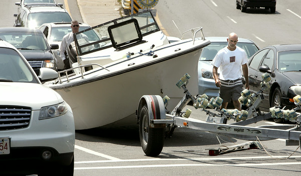KEN YUSZKUS/Staff photo. Bob Ellis, right, is the owner of the boat that broke loose from the trailor and landed on Cabot Street at the foot of the bridge in Beverly. It tied up traffic for a short time until a large forklift removed the boat from the scene.  8/5/14