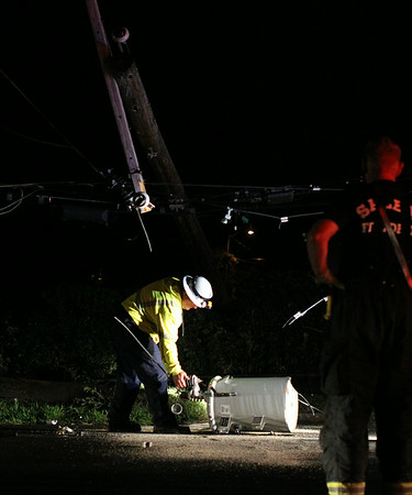 A National Grid worker picks up a transformer which fell from a telephone pole after it was taken out by an erratic truck which smashed through the fence and into Greenlawn Cemetery early Thursday morning. DAVID LE/Staff photo. 8/7/14.