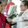 KEN YUSZKUS/Staff photo. Rose Abad of Beverly, has her blood pressure checked by RN Sandra Lustenberger at the Senior Day In The Park event held at Lynch Park in Beverly. 8/7/14
