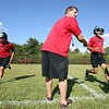Salem High School football coach Greg Gibson shouts instructions to a few players during a drill on the first day of camp on Monday afternoon. DAVID LE/Staff photo. 8/18/14.