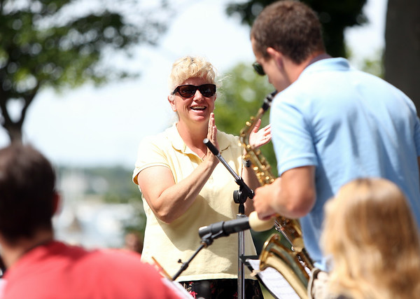 Salem High School Jazz Band Director Cynthia Napierkowski applauds a soloist during the Salem Jazz and Soul Festival at the Bandstand at Salem Willows on Saturday morning. DAVID LE/Staff  photo. 8/16/14.