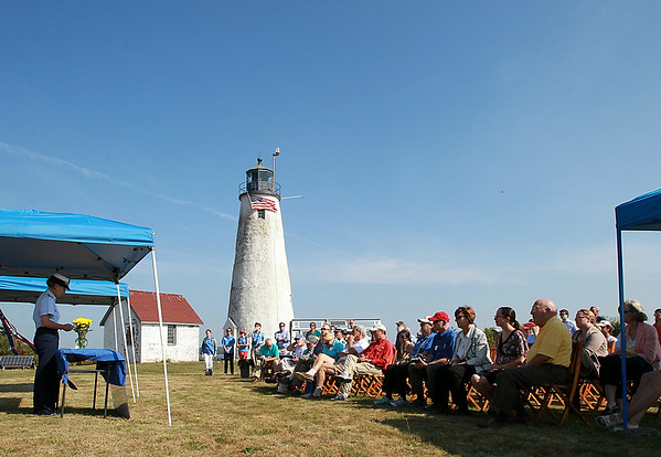 A large crowd gathered in front of the light house on Baker's Island listen to Rear Admiral Linda Fagan of the Coast Guard speak during a short ceremony in which a portion of Bakers Island was transferred from the US Coast Guard to the Essex National Heritage Commission on Wednesday morning. DAVID LE/Staff photo. 8/27/14.