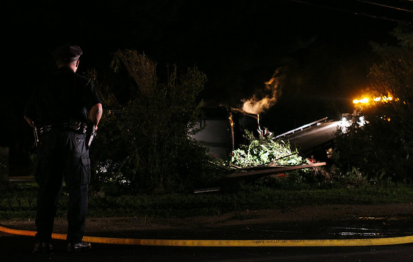 A Salem Police officer stands guard and looks on as the engine of a flipped over Chevy Silverado begins to smoke and eventually catch fire as it was being removed from the Greenlawn Cemetery outskirts. DAVID LE/Staff photo. 8/7/14.