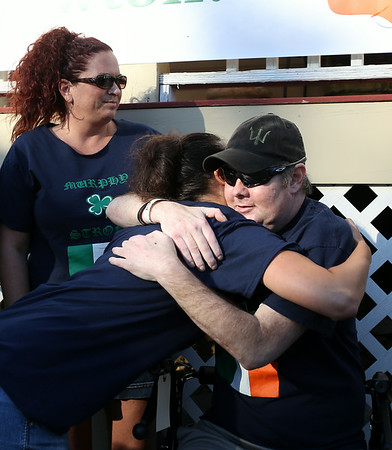 Newton Murphy, Deputy Sheriff of Essex County, gets a hug from his cousin Kelly DiMarino, left, after Murphy returned home on Tuesday afternoon. Murphy had been in rehab for over three months, recovering from a double lung transplant and this was his first time home since the surgery. DAVID LE/Staff photo. 8/19/14