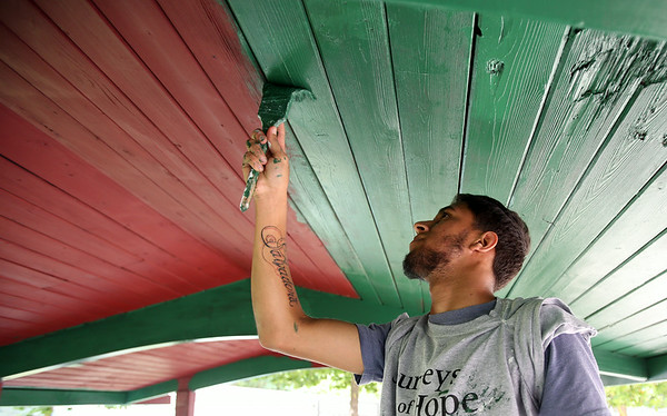 Endis Soto, a part of a youth group for at-risk and underserved kids called Journeys of Hope, paints the roof of a gazebo at Charles Curtis Memorial Park in Salem on Thursday afternoon. DAVID LE/Staff photo. 8/21/14.