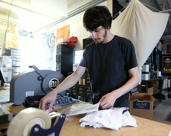 Corey Archambault, an employee at DeathWish Inc. in Beverly puts together an order on Friday afternoon inside their warehouse on Park Street in Beverly. DAVID LE/Staff photo. 8/1/14.