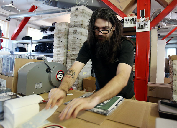 James Garvey, an employee at DeathWish Inc. packages an order on Friday afternoon. DAVID LE/Staff photo. 8/1/14.
