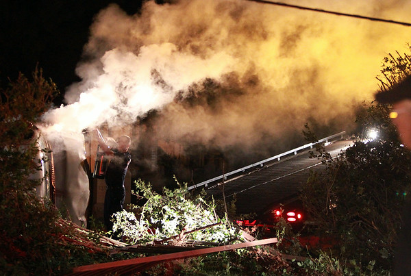 A Salem firefighter tries to extinguish some of the smoke pouring from a flipped over pickup truck in Greenlawn Cemetery after it flipped over and crashed there early Thursday morning. . DAVID LE/Staff photo. 8/7/14.