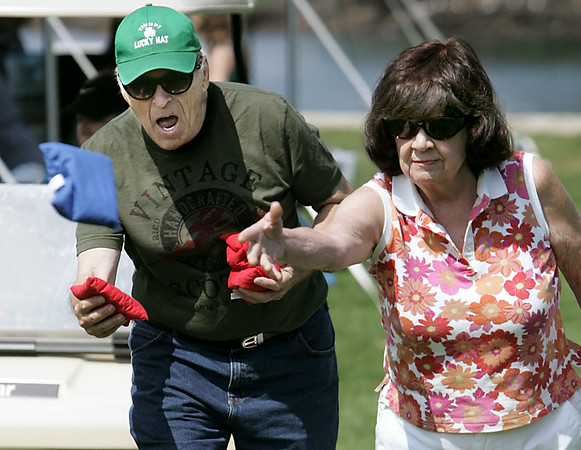 KEN YUSZKUS/Staff photo. Dale Carver and Ellen Appolloni, both of Beverly, toss bean bags which was part of the lawn games at the Senior Day In The Park event held at Lynch Park in Beverly. 8/7/14