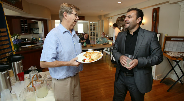 KEN YUSZKUS/Staff photo.  Rotary member Andy Stone speaks with Jamal Taha of Iraq at the start of the Marblehead Rotary Club held at the Boston Yacht Club in Marblehead. 8 Iraqis at Salem State were here under a Fulbright speaking to the club. 8/14/14