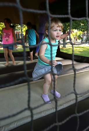 KEN YUSZKUS/Staff photo. Stella Riccardi, 2, jumps in one of the moon bounces at Kids' Night on Salem Common. The Salem YMCA transformed the Salem Common into a paradise for children with moon bounces, rides, games, and arts and crafts.  8/8/14