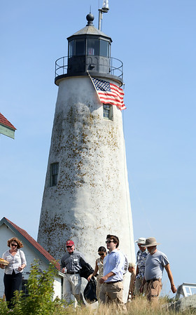 Members of the Essex National Heritage Commission, and General Services Administration file past the lighthouse on Bakers Island following a short ceremony in which the deed for part of the island was transferred from the US Coast Guard to the Essex National Heritage Commission. DAVID LE/Staff photo. 8/27/14.