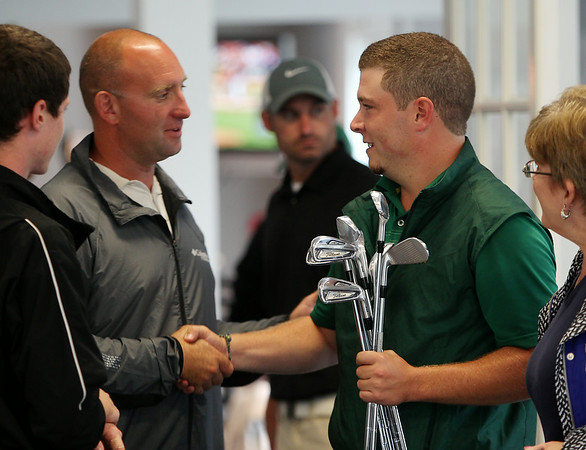 Winner of the 2014 North Shore Amateur Open Nick Maccario, right, shakes hands with one of his competitors after being awarded a set of victory clubs in the clubhouse at Far Corner Golf Course in Boxford on Wednesday afternoon. DAVID LE/Staff photo. 8/13/14.