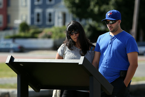 Vince and Melissa Raponi, visiting Salem from Toronto, read a sign in front of the Friendship in Salem on Monday afternoon. DAVID LE/Staff photo. 8/18/14.