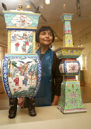 """KEN YUSZKUS/Staff photo. Daisy Yiyou Wang is a new curator of Chinese and East Asian art at PEM, who has curated a new installation of Chinese art from the museum's collection, """"Double Happiness: Celebration in Chinese Art,"""" which examines how festivals, ceremonies and celebrations have long inspired creative expression in Chinese culture. She is near the exhibit of altar sets with incense burner, candleholders, and vases with Daoist figures, flowers, birds, and characters of longevity. 8/4/14"""