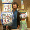 "KEN YUSZKUS/Staff photo. Daisy Yiyou Wang is a new curator of Chinese and East Asian art at PEM, who has curated a new installation of Chinese art from the museum's collection, ""Double Happiness: Celebration in Chinese Art,"" which examines how festivals, ceremonies and celebrations have long inspired creative expression in Chinese culture. She is near the exhibit of altar sets with incense burner, candleholders, and vases with Daoist figures, flowers, birds, and characters of longevity. 8/4/14"
