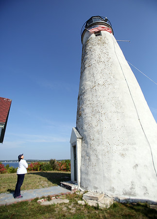 Salem Mayor Kim Driscoll peers up at the lighthouse on Bakers Island following a ceremony on Wednesday morning. DAVID LE/Staff photo. 8/27/14.