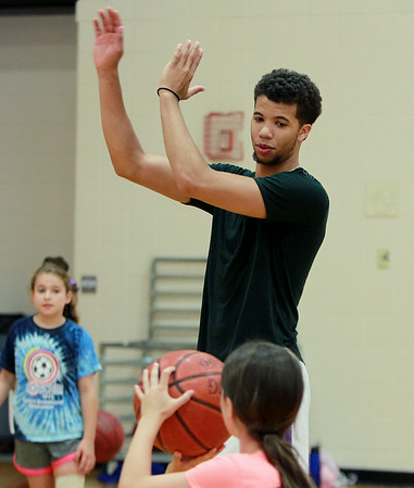 Michael Carter-Williams, a Hamilton native and guard for the Philadelphia 76ers, instructs campers on shooting technique during the MCW Basketball Camp held at Ipswich High School over a three-day span. DAVID LE/Staff photo. 8/14/14.