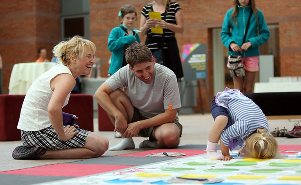 Three-year-old Lily Freitas, right, tries to figure out how to balance while playing twister, as her father Art, and her grandmother Kayla Kirkpatrick, of Salem, smile at her attempt at the Peabody Essex Museum's Throwback Game Night on Thursday evening. DAVID LE/Staff photo. 8/21/14.