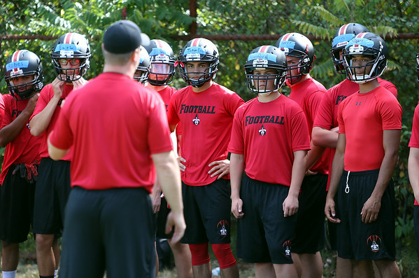 Members of the Salem High School football team listen to new Head Coach Matt Bouchard as he gives the team a talk prior to the start of practice on Monday afternoon. DAVID LE/Staff photo. 8/18/14.