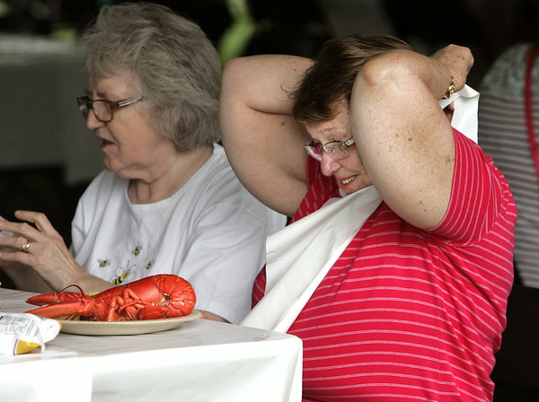 KEN YUSZKUS/Staff photo. Lucille Walkup, right, ties on a bib before attacking a lobster at the Beverly Homecoming Lobster Festival. Sandra Maidment is on the left. 8/6/14