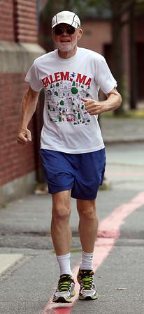 DAVID LE/Staff photo. Joel Caron, of Salem, runs along Brown Street in Downtown Salem on Thursday afternoon. 8/20/15.