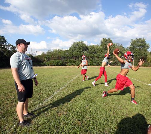 DAVID LE/Staff photo. Salem head coach Matt Bouchard runs his quarterbacks through drills at camp on Wednesday afternoon. 8/26/15.