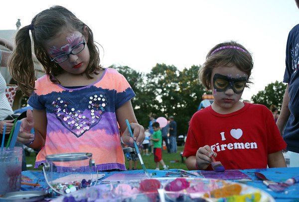 DAVID LE/Staff photo. Sisters Hayley, left, and Teagan Pelletier, of Salem, paint tile squares at the first annual National Night Out hosted by the Salem Police Department at the Salem Commons on Tuesday evening. 8/2/16.