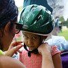 DAVID LE/Staff photo. Luna Flores, 3, of Lynn, gets a helmet adjusted on her head by Melissa Wilson, of Mass in Motion Salem. 8/9/16.