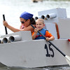 DAVID LE/Staff photo. Cait and Ben Gaglione, 4, paddle from the front of their cardboard boat, while Anthony Gaglione paddles from the back. 8/7/16.