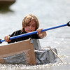DAVID LE/Staff photo. Eight-year-old Harry Wilson, of Beverly, paddles his cardboard boat towards the finish line during the annual races held at Lynch Park in Beverly. 8/7/16.