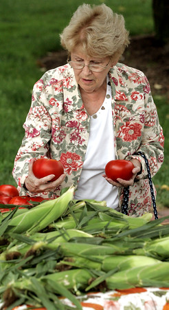 KEN YUSZKUS/Staff photo.         Fran Cushing of Beverly looks over some tomatoes before purchasing some at the Beverly Farmers Market.  08/01/16