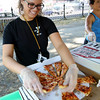 KEN YUSZKUS/Staff photo.   Cristina Diisso divides up the slices of cheese pizza at one of the tents during the start of Salem's Best Pizza competition held on the Salem Common.  08/08/16