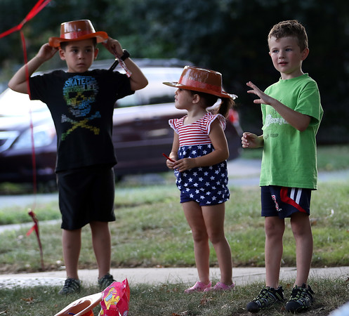 DAVID LE/Staff photo. Johnny, 6, and Mia Mancini, 3, left, and Johny McGinnity, 4, all of Danvers, stand on Park Street and watch the annual Danvers Parks and Rec parade on Thursday evening. 8/18/16.