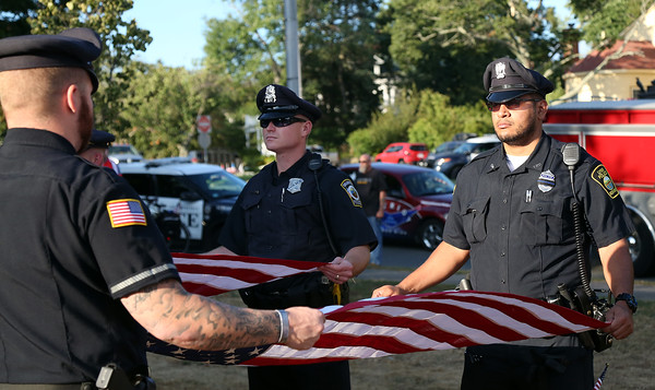 DAVID LE/Staff photo. Officers Steven Luck, of Swampscott, left, and Jeffrey Aceituno, of Lynn, prepare to fold flags during a short ceremony held at the Swampscott Monument. 8/7/16.