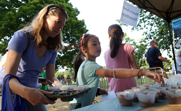 DAVID LE/Staff photo. Emily Zisson, 6, of Marblehead, picks out an ice cream selection as her mom Laura, holds a tray full of ice cream treats. 8/9/16.