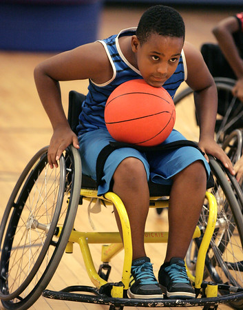 KEN YUSZKUS/Staff photo.    Adonis Valenzuela holds the ball under his chin while racing toward the basket during a basketball game using a high-tech, modified wheelchair that was one of many Spaulding Rehab brought to try out.  08/04/16