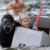 DAVID LE/Staff photo. Paikea Paddol, 5, of Beverly, happily peers out of her cardboard boat while being motored along by her father Jon at the annual cardboard boat races at Lynch Park in Beverly. The Paddol's were dressed up as Kylo Ren and Rey from the latest Star Wars movie. 8/7/16.