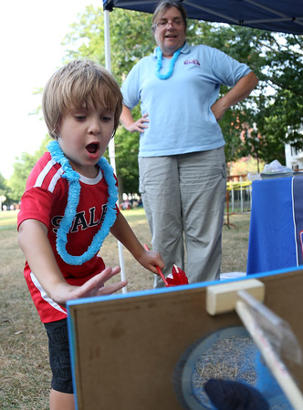 DAVID LE/Staff photo. Five-year-old Eli Wettengel, of Salem, tosses a bean bag through a hole to win a prize at the annual Ice Cream Bowl at the Salem Common on Tuesday evening. 8/9/16.