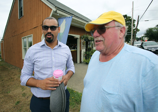 KEN YUSZKUS/Staff photo.    Peabody city planner Pedro Soto, left, talks with Tillie's Farm owner Earl Spurr in front of his farm stand on Lynn Street in Peabody.  08/01/16