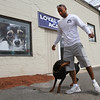 Jermaine Anderson has his doberman pinscher run through his legs as he walks fast outside his new dog training business, Loyal Canines, Thursday, July 28, in Peabody.