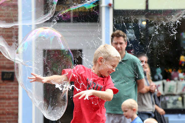 DAVID LE/Staff photo. Seven-year-old Caleb O'Brien winces as he pops a bubble along the Essex Street Pedestrian walkway. 8/13/16.