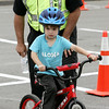KEN YUSZKUS/Staff photo.    Beverly patrolman Timm Mezzo talks Luke Pescatore, 4, through the bicycle obstacle course at Lynch Park. The bike safety rodeo was part of Beverly Homecoming events.  08/01/16