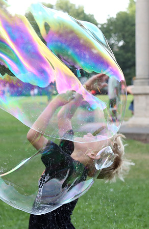 DAVID LE/Staff photo. Jacob Riley, 7, of Salem, finds himself immersed in a large bubble at the annual Ice Cream Bowl at Salem Common on Tuesday evening. 8/9/16.