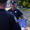 DAVID LE/Staff photo. Officer Chuck Sinclair, of the Marblehead Police Department, prepares to fold a flag. 8/7/16.