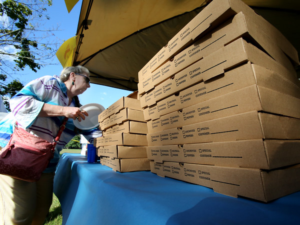 KEN YUSZKUS/Staff photo.   Large stacks of boxes of pizza surround Shelia Della Croce of Lynn, as she orders at one of the tents during Salem's Best Pizza competition held on the Salem Common.  08/08/16